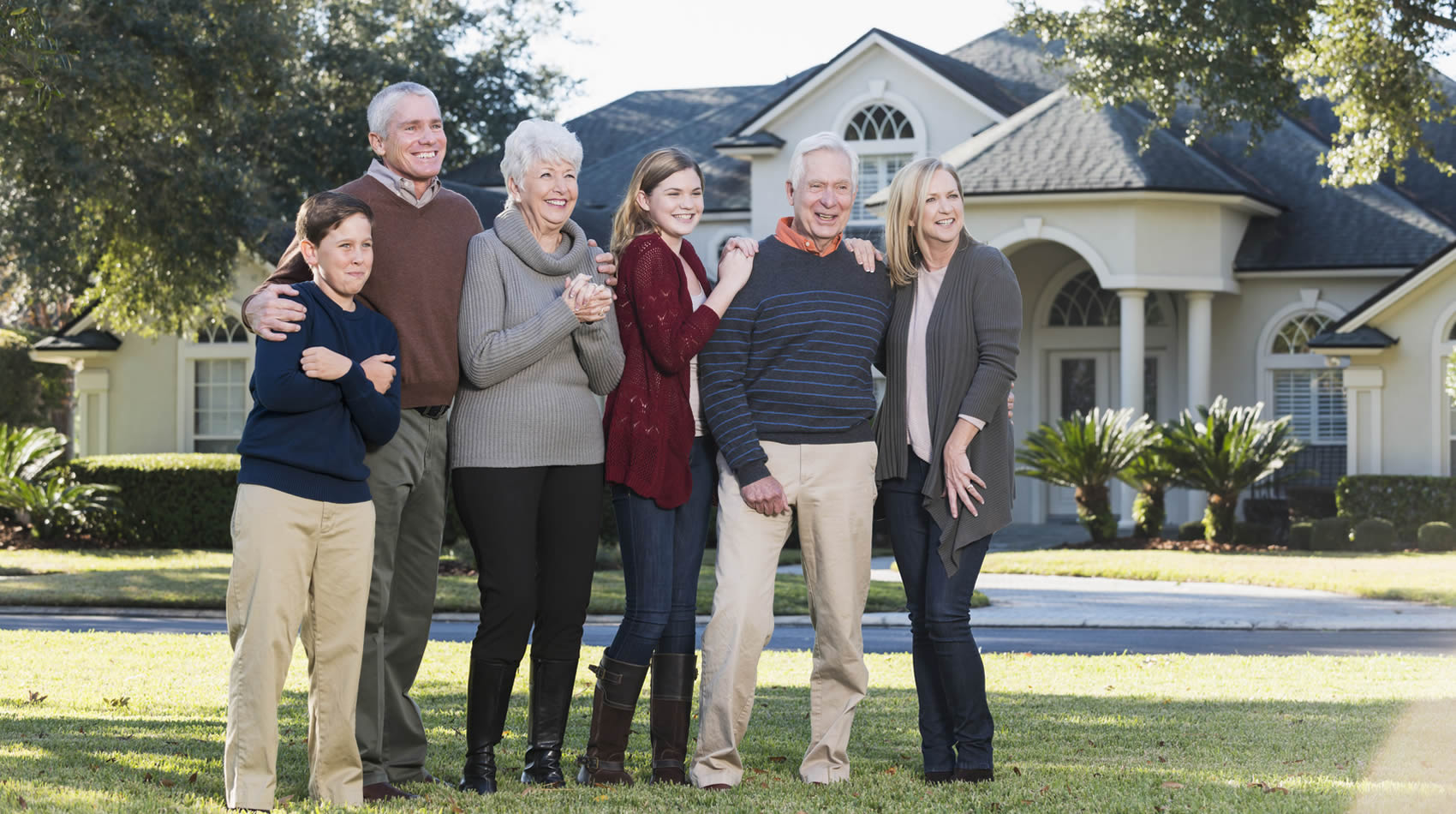 Multigeneration family standing in the front yard